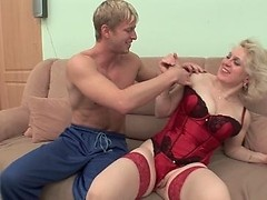 Blonde granny in hot red lingerie plays with a hunk