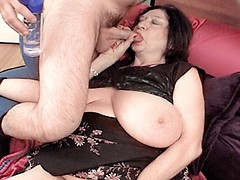 Brunette granny with huge melons receiving a hard fuck from two studs